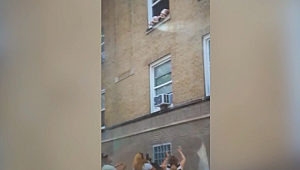 Authorities investigating after toddlers seen hanging from second-story window